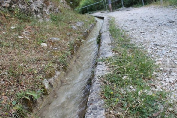 The first sign of water.  Excess water runs along a channel by the side of the path.