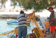 A fisherman untangles his nets at Aghios Antonis
